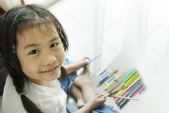 Face of asian children playing color pencil on floor. Face of asian children   playing color pencil on floor Royalty Free Stock Image