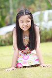 Face of Asian girl with long hair sitting on green grass field Royalty Free Stock Photography