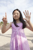 Face of asian girl show finger acting as a symbolic of number Stock Photography