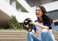 Face of asian teenage like to take photo. Select focus happy face of asian teenage like to take photo with camera to be stocker gig economy Stock Image