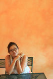 Face of asian woman sitting  in front of orange ce Stock Image