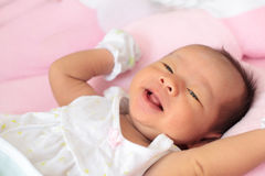 Face of baby infant. Lying on bed with happy face Royalty Free Stock Photos