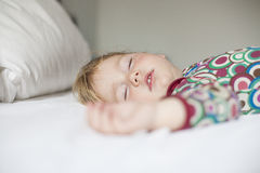 Face of baby sleeping. Blonde caucasian baby face nineteen month age with colored shirt sleeping on white sheets king bed royalty free stock photo