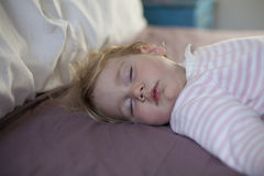 Face of baby sleeping on king bed. Blonde caucasian baby nineteen month age with pink and white stripped jersey sleeping on brown sheets queen bed royalty free stock photos