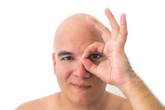 Face of a bald man in white background. With a hand on one eye Stock Photo