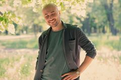 Face of a bearded smiling bald man in the park. Portrait of a middle-aged man stock photo