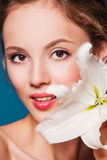 The face of a beautiful girl with fresh flower lily Stock Images
