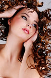 Face of the beautiful girl with  long curly hairs Royalty Free Stock Images