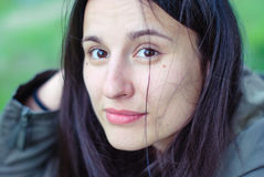 The face of a beautiful girl without makeup with black eyes and hair with freckles. Royalty Free Stock Image
