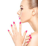 Face of a beautiful  girl with pink  nails on white background. Profile face of a girl with pink nails. Fashion model posing on white background Stock Photography