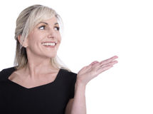 Face of a beautiful older woman looking sideways and presenting. Face of a beautiful older woman looking sideways and presenting with her hand stock images