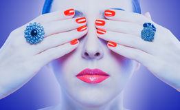 Face and beautiful red manicure on the blue Royalty Free Stock Photos