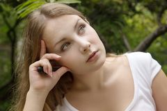 Face of beautiful serious girl in green summer park Royalty Free Stock Photo