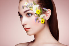 Face of beautiful woman decorated with flowers Royalty Free Stock Image