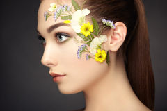 Face of beautiful woman decorated with flowers Royalty Free Stock Photography