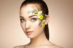 Face of beautiful woman decorated with flowers Stock Photography