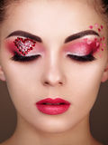 Face of beautiful woman with holiday makeup heart. Beauty fashion. Lips in red lipstick. Eyelashes. Cosmetic Eyeshadow. Makeup detail Stock Photos
