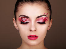 Face of beautiful woman with holiday makeup heart. Beauty fashion. Lips in red lipstick. Eyelashes. Cosmetic Eyeshadow. Makeup detail Stock Images