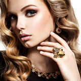 Face of  beautiful woman with long hair and gold jewelry Stock Images