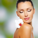 Face of  beautiful woman with a white orchid flower Stock Photo