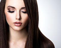 Face of beautiful young woman with brown make-up and straight royalty free stock images