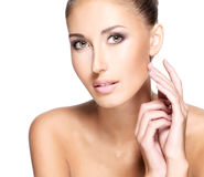 Face of a beautiful young woman with clear fresh skin touching h Stock Photos