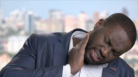Face of black businessman with nape pain. Close up dark-skinned man in business suit suffering from terrible neck pain. Stress, fatigue, illness stock footage