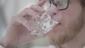 Close up face of blond bearded thoughtful man in glasses drinking water from the glass close up. Handsome businessman. The face of the blond bearded thoughtful stock video footage