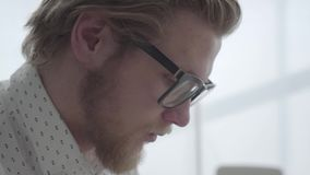 Face of blond thoughtful man in glasses sitting in a light comfortable office. Handsome businessman working. Side view. Face of blond thoughtful man in glasses stock video footage