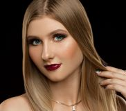 Face, blue eyes, black background. Beautiful face woman, has blue contact lenses in eyes, red make up, long eyelashes, long blonde hair, luxury shine Stock Photos