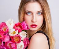 Face, blue eyes, tulips Stock Photos