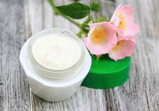 Face and body cream  with dog rose, also known wild rose, lat. Rosa canina in  romantic style Royalty Free Stock Photography