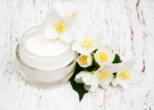 Face and body cream moisturizers with jasmine flowers on white w Royalty Free Stock Images