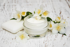 Face and body cream moisturizers with jasmine flowers on white w Stock Photos