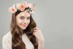 Face bonita Mulher bonita com pele clara, cabelo encaracolado e flores no fundo branco da bandeira fotografia de stock royalty free