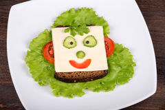 Face on bread, made from cheese, lettuce, tomato, cucumber and pepper. Royalty Free Stock Image