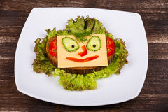 Face on bread, made from cheese, lettuce, tomato, cucumber and pepper. Stock Photo