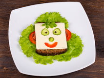 Face on bread, made from cheese, lettuce, tomato, cucumber and pepper Stock Images