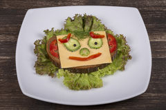 Face on bread, made from lettuce, tomato, cucumber and pepper. Royalty Free Stock Photography