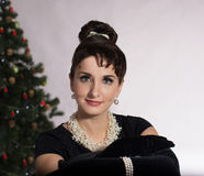Face Brunette on the background of Christmas tree. Beautiful woman in the image of Audrey . Retro Style Stock Photography
