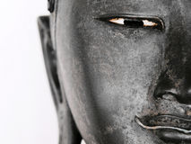 Face of Buddha. Half Face of a Buddha Statue Isolated on a White Background Royalty Free Stock Photo