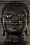 Face of Buddha on brick wall. Royalty Free Stock Photos
