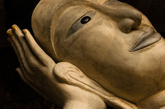 Face of Buddha statue reclining on hand. Against black background Stock Images