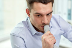 Face of businessman with phone receiver in office. Business, people and communication concept - face of businessman with phone receiver in office Stock Images