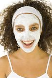Face care mask. Young happy woman with white purifying mask. She looking at camera Royalty Free Stock Photos