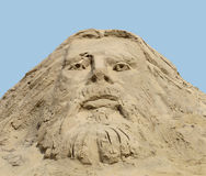 Face carved in a sand pile. Stock Images