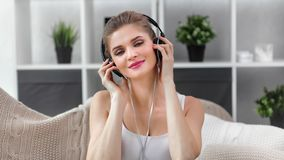 Face of charming smiling girl listening music using headphones dancing having fun at home close-up. Face of charming smiling girl listening music using stock video