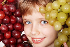 Face of child girl with grapes. Royalty Free Stock Photography