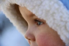 Face of a child in the hood in winter stock photos