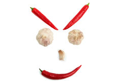 Face from chili pepper and garlic on a white background Stock Images